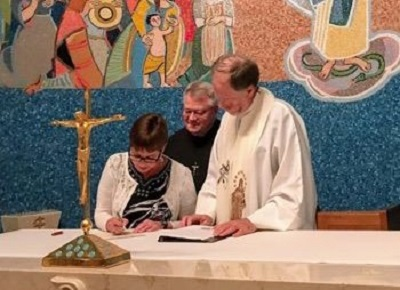 US Oblate Provincial Secretary Laura Glasgow, new US Provincial Fr. Louis Studer, OMI and Oblate General Councilor for US/Canada Warren Brown, OMI sign documents after Fr.Studer's installation ceremony at the Oblate Chapel.
