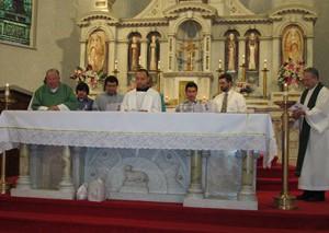 Mano Romero (Ctr.) leads prayer, Fr. Richard Sudlik (far left,) Fr. Louis Lougen (far right)